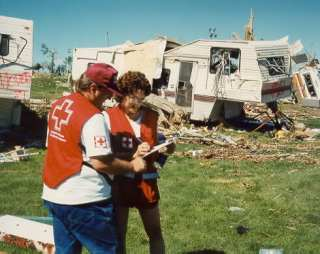 Red Cross Staffer Leslie Vryenhoek and amateur radio operator Darren Misik VE6ZZM compare notes at devastated campsite.