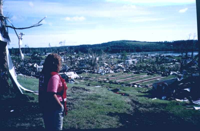Red Cross worker views the damage in daylight.
